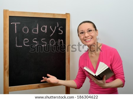 Woman teacher in glasses smiling about school board, book in hand