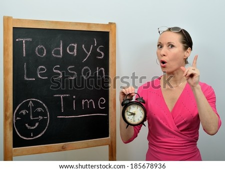 Woman teacher in school tells a subject about time - stock photo