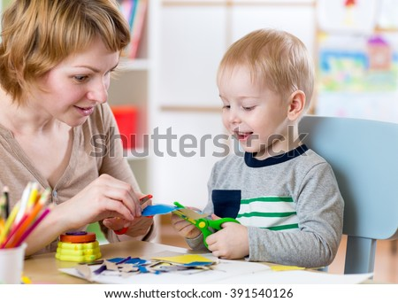 Woman teaches child handcraft at kindergarten or playschool or home - stock photo