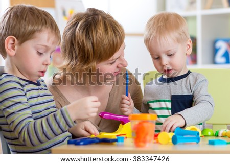 woman teaches children handcraft at kindergarten or playschool