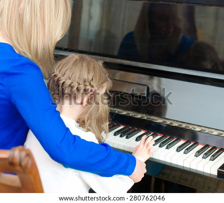 Woman teaching little girl to play the piano. - stock photo