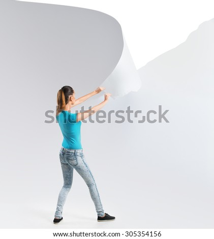 Woman tearing a white paper background   - stock photo