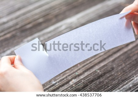 woman tearing the white paper