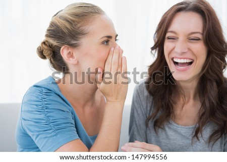 Woman telling secret to her friend and sitting on the sofa - stock photo