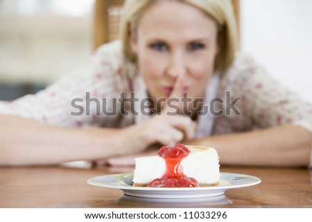 Woman Tempted By Slice Of Strawberry Cheesecake - stock photo
