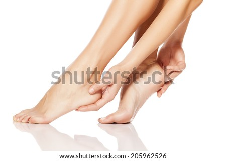 woman tenderly touching her feet - stock photo