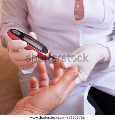 Woman testing for high blood sugar. Woman holding device for measuring blood sugar - stock photo