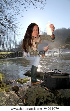 Woman testing quality of natural water - stock photo