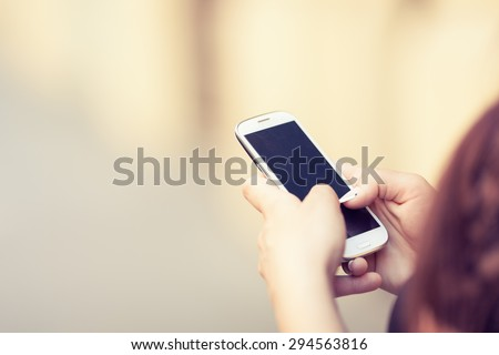 Woman texting message on her mobile phone. Toned photo, shallow depth of field. - stock photo