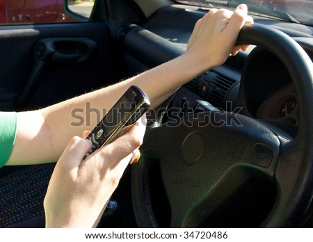 Woman texting while driving a car - stock photo