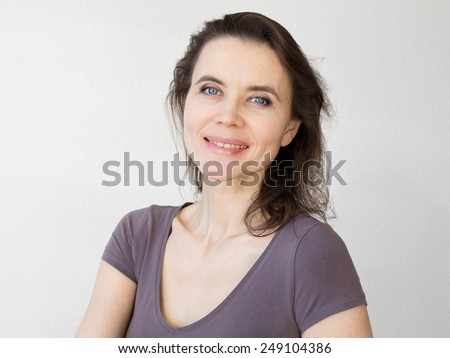 Woman thinking about and looking into camera - stock photo