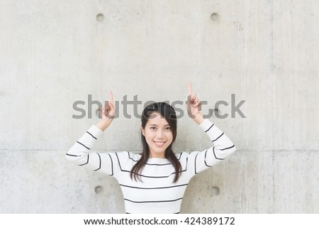Woman thinking against concrete wall - stock photo