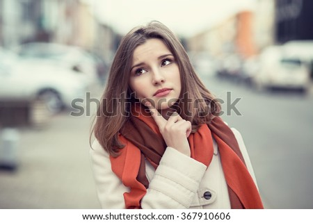Woman thinking. Closeup portrait headshot face beautiful confident serious thoughtful young lady girl finger on cheek isolated cityscape outdoor background. Multicultural mixt race asian russian model - stock photo