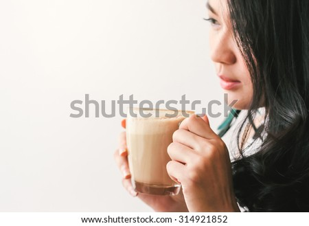 Woman thinking while drinking hot latte coffee at cafe - stock photo
