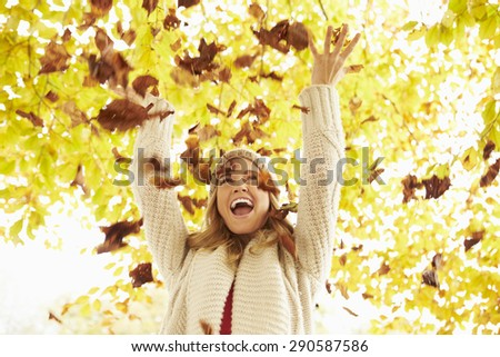 Woman Throwing Autumn Leaves Into The Air - stock photo