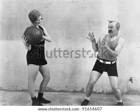 Woman throwing ball to nervous man - stock photo
