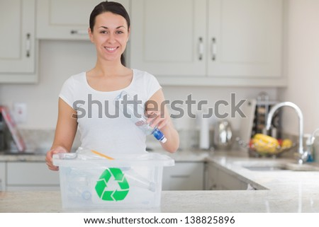 Woman throwing bottle into recycling bin in kitchen - stock photo