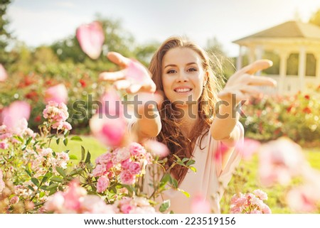 woman throwing rose petals - stock photo