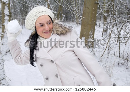 woman throwing snowball in snow covered forest - stock photo