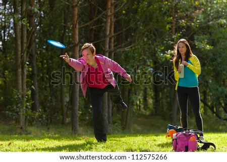 Woman throws a disc, friend waiting on background