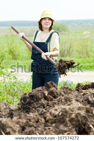 woman throws the manure pitchfork in the field - stock photo