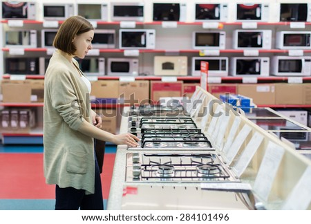woman to buy the stove - stock photo
