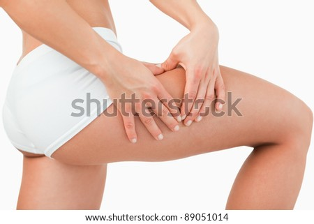 Woman touching her thigh against a white background - stock photo
