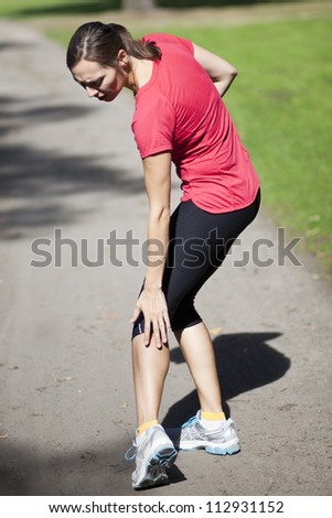woman touching her thigh because of pain - stock photo