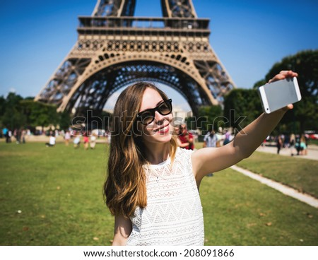 Woman tourist at Eiffel Tower smiling and making travel selfie. Beautiful European girl enjoying vacation in Paris, France - stock photo