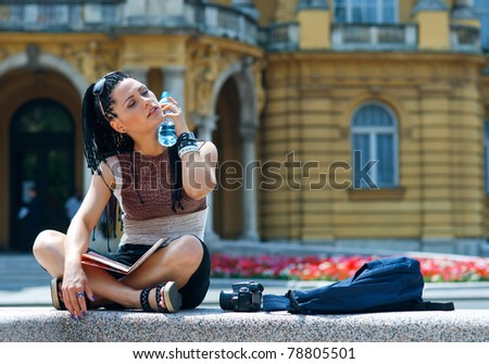 woman tourist cooling herself with water bottle - stock photo
