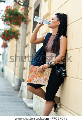 woman tourist drinking water from bottle and relaxing - stock photo
