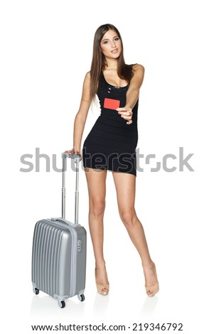 Woman tourist. Full length sexy young woman in black mini dress standing with suitcase and showing blank credit card, isolated on white background - stock photo