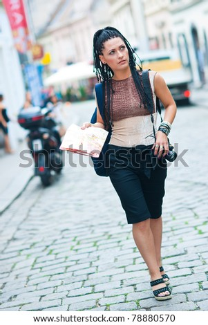 woman tourist holding map and walking in the city street
