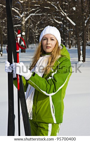 Woman tourist skier in snowy forest with ski poles