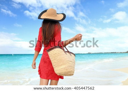 Woman tourist walking on tropical summer vacation wearing sun hat, red dress and beach bag relaxing on travel holidays. Young lady from behind in luxury fashion beachwear. - stock photo