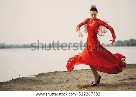 woman traditional dancer wearing colorful dress on the beach