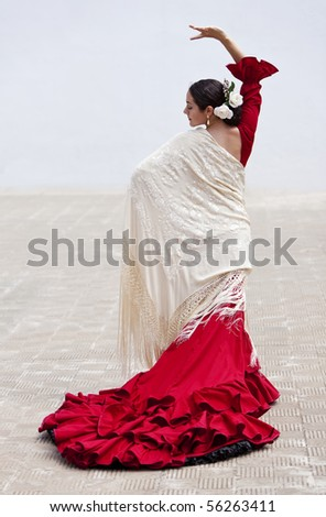Woman traditional Spanish Flamenco dancer dancing outside in a red dress with a cream colored shawl - stock photo