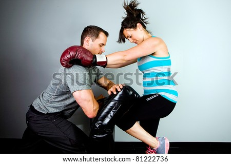 Woman training to fight with a man in a gym. - stock photo