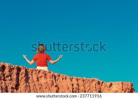 Woman training yoga and meditation on the cliff of mountain - stock photo