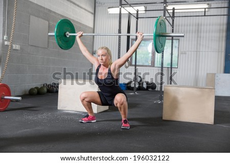 Woman trains squats at crossfit center - stock photo