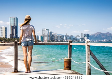 Woman traveler enjoying beautiful view from the wooden pier, big city on the background