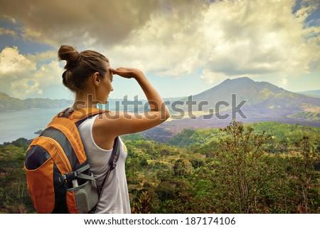 Woman traveler looking at Batur volcano. Indonesia - stock photo