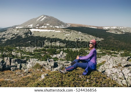 Woman Traveler resting on a rock. Hiking and Travel Lifestyle concept