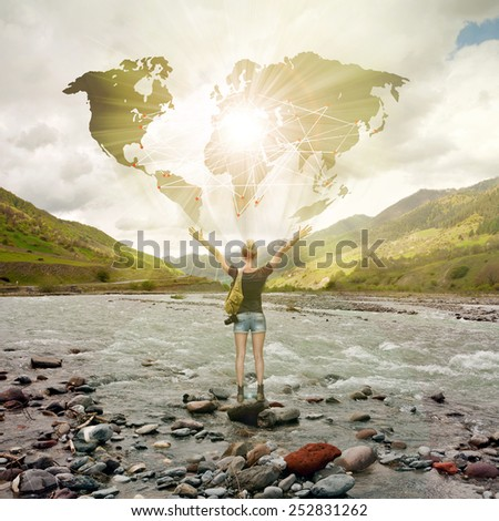 Woman traveler standing at sunset in front of world map - stock photo