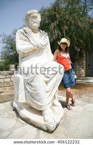 woman traveler tourist leaning on marble roman man statue, from V century B.C., behind Ayios or Agios Titos Basilica at ancient city Gortyn, greek monument in Crete, Greece Europe - stock photo