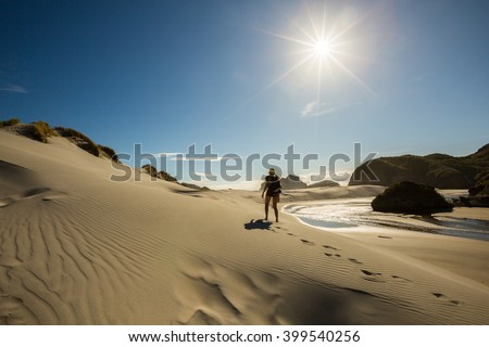 Woman traveler walking on sand dune at Wharariki Beach in New Zealand