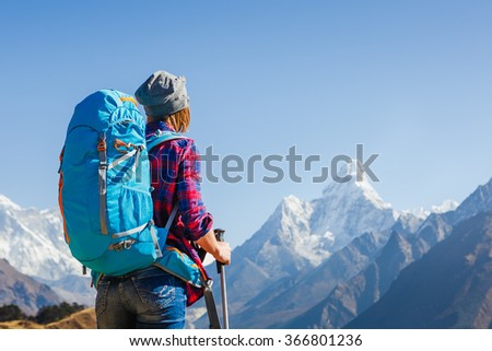 Woman Traveler with Backpack hiking in Mountains with beautiful Himalaya landscape on background mountaineering sport lifestyle concept