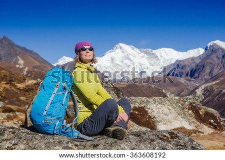 Woman Traveler with Backpack hiking in Mountains with beautiful summer Himalayas landscape on background  - stock photo