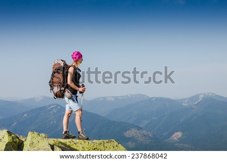 Woman Traveler with Backpack hiking in Mountains with beautiful summer landscape on background - stock photo