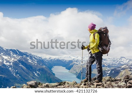 Woman Traveler with Backpack hiking in the Mountains Yotunheimen national park. Norway - stock photo